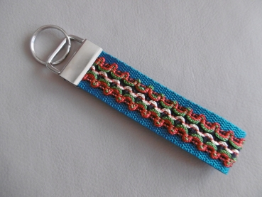 Key chain with decorative ribbon and metal clasp silver colors